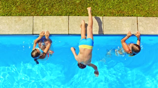 slo mo cs boy jumping in the pool doing a front flip - jumping stock videos & royalty-free footage
