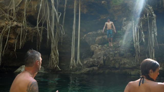 ms boy jumping into cenote while on vacation with family - carefree stock videos & royalty-free footage