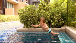 Boy jumping into outdoor swimming pool in tropical resort