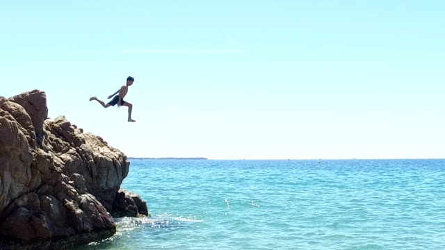 Boy jumping into the sea. Slow motion