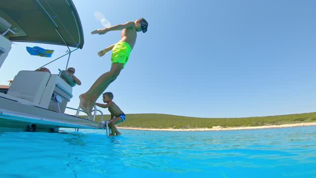vídeos de stock, filmes e b-roll de menino pulando de um barco em água azul e mãe observando do barco - nautical vessel