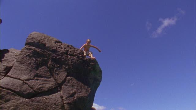 SLO MO, WS, LA, Boy (8-9) jumping off rock into ocean, Oahu's North Shore, Hawaii, USA