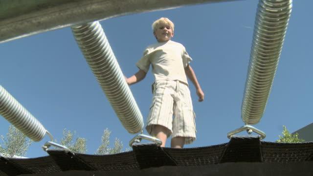 boy jumping on a trampoline - pedana elastica per saltare video stock e b–roll
