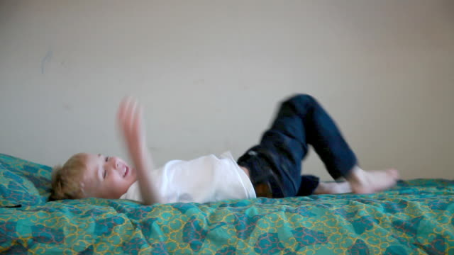Boy jumping onto bed