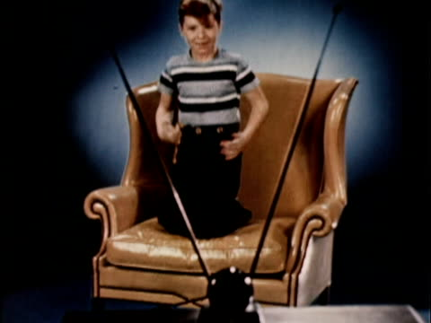 vídeos de stock e filmes b-roll de 1956 ws boy jumping up and down on wingback leather chair while watching tv / usa - ecstatic