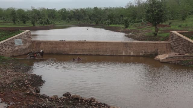 a boy jumps into a pond formed after the ridge to valley water harvesting approach was implemented in dewas madhya pradesh india on monday july 4 a... - madhya pradesh stock videos and b-roll footage