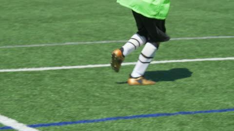 vidéos et rushes de a boy kicking a ball at youth soccer football goalie goalkeeper on a turf grass field. - slow motion - ball