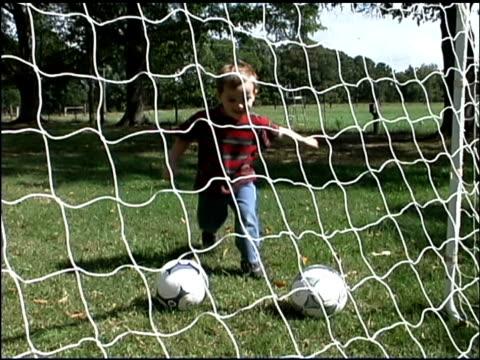 boy kicking soccer goal - soccer goal stock videos & royalty-free footage