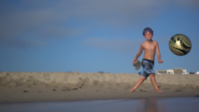 A boy kicks a soccer ball into the waves at the beach.