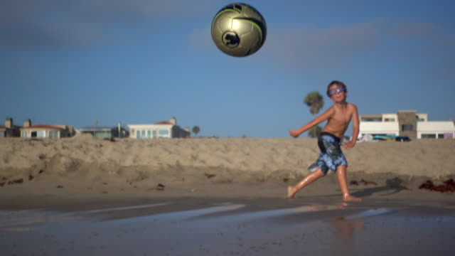 vidéos et rushes de a boy kicks a soccer ball into the waves at the beach. - 8 9 ans