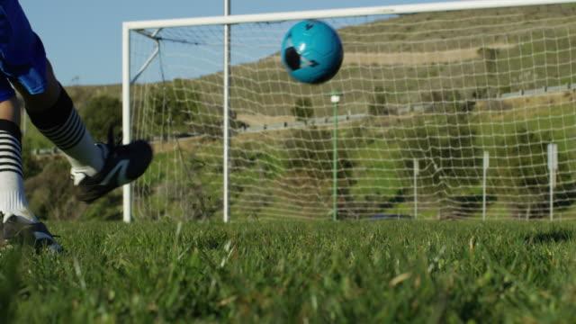 Boy kicks soccer ball to goal