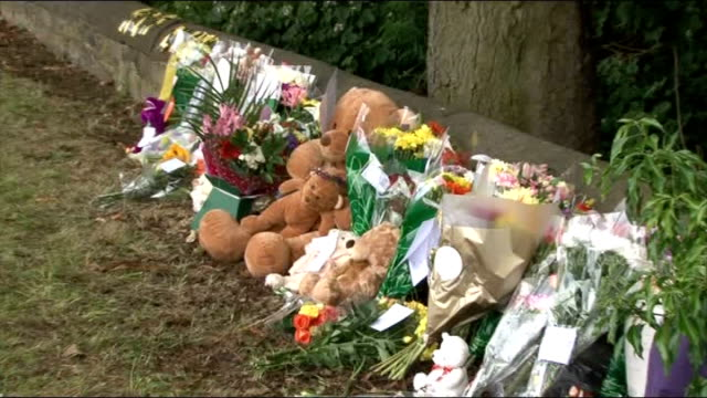 stockvideo's en b-roll-footage met boy killed by hitandrun driver in wakefield england west yorkshire wakefield ext people looking at floral tributes and messages left in memory of boy... - kant van de weg