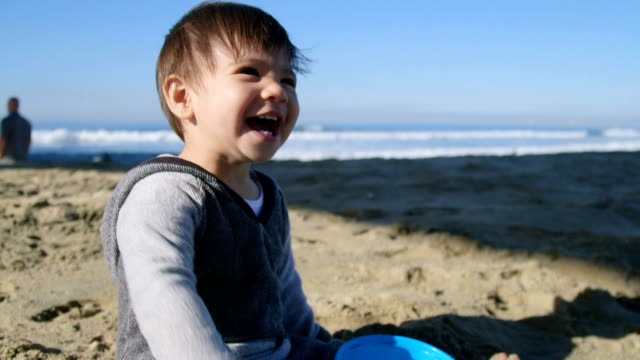 boy laughs while throwing sand - huntington beach california stock videos and b-roll footage