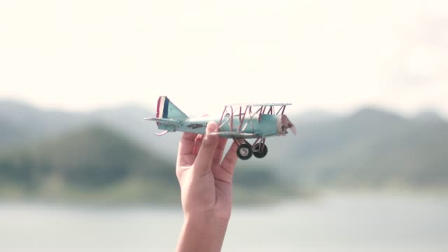 A boy launches a toy airplane in the sky with mountain background