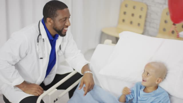 Boy pose dans son lit d'hôpital avec ballon
