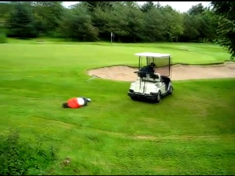 / boy laying on top of golf cart / cart goes down hill and kid gets thrown off the cart and lays on the ground in pain. golf cart planking stunt on... - golf cart stock videos & royalty-free footage