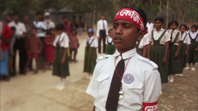 MS, SELECTIVE FOCUS, Boy (12-13) leading girls (12-15) during practice drill at assembly on field, Mawna, Bangladesh
