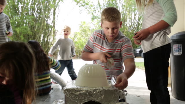 Boy leading group of young kids building a robot with recycled materials.