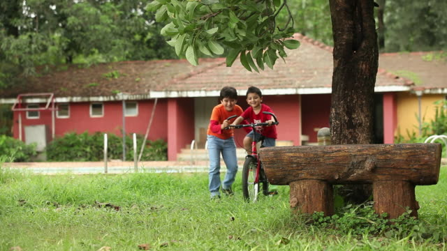 Boy learning bicycle with the help of his friend