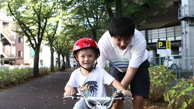 a boy learning how to ride a bike from his father - son点の映像素材/bロール