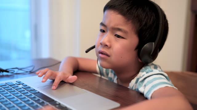 vídeos de stock, filmes e b-roll de boy learning online with computer and boring - frustração