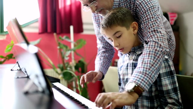 vídeos de stock e filmes b-roll de boy learning the piano with her teacher - pianista