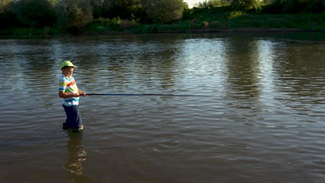 vídeos de stock e filmes b-roll de boy learning to catch a fish - peixe fresco