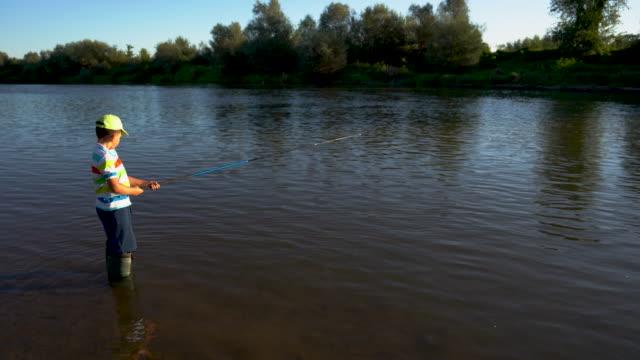 魚を捕まえることを学ぶ少年 - 獲った魚点の映像素材/bロール