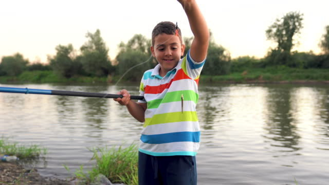 boy learning to catch a fish - first occurrence stock videos & royalty-free footage