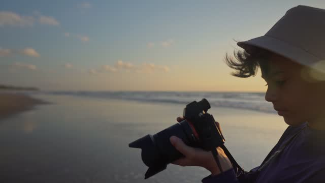 boy learning to photograph on the beach - photographer stock videos & royalty-free footage