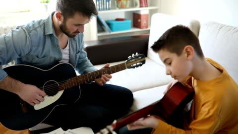 junge, lernen, gitarre zu hause zu spielen - teaching stock-videos und b-roll-filmmaterial