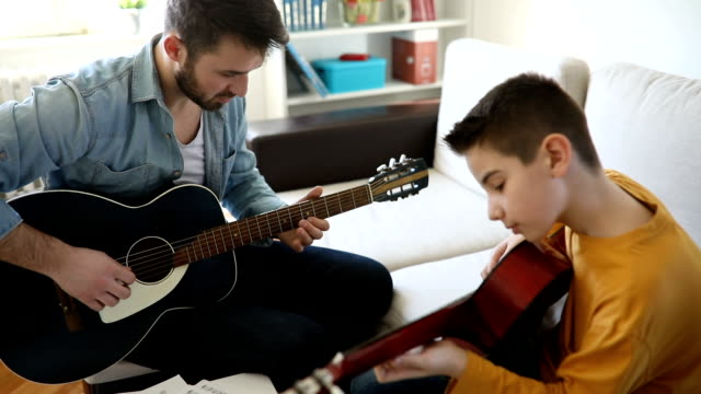 Boy learning to play guitar at home