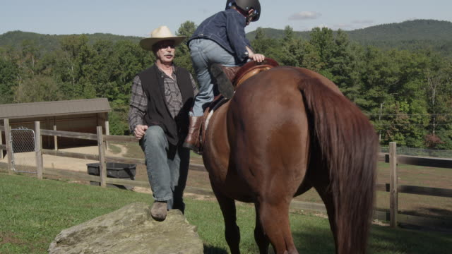 A boy learns how to mount and dismount a horse.