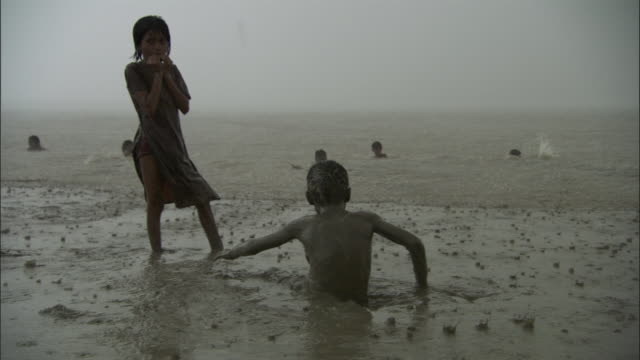 vídeos de stock e filmes b-roll de boy lies in mud in pouring rain, ganges available in hd. - monção
