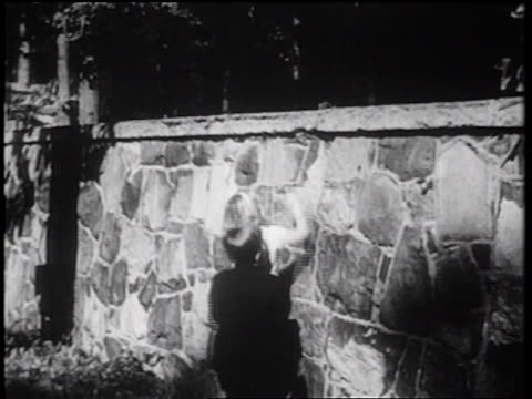 b/w 1939 rear view boy lifting little girl over stony wall / documentary - stone wall stock videos & royalty-free footage