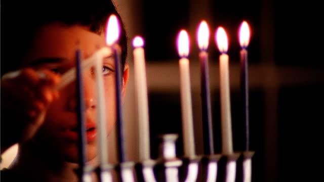 boy (10-12) lighting candles of menorha - 10 11 år bildbanksvideor och videomaterial från bakom kulisserna