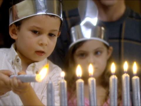vídeos de stock, filmes e b-roll de cu boy (4-5) lighting hanukkah candles / beit yitzhak, israel - candelabro
