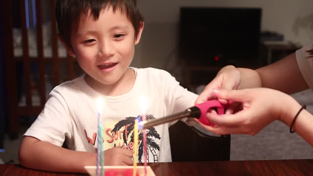 a boy lights a birthday cake candle with his mother - birthday cake stock videos & royalty-free footage