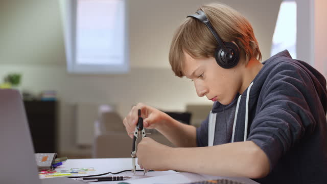 boy listening to an online lesson and working with a pair of compasses - pair of compasses stock videos & royalty-free footage