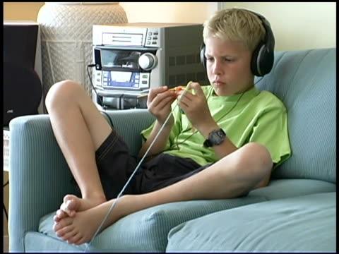 boy listening to headphones and crocheting - 男児のみ点の映像素材/bロール