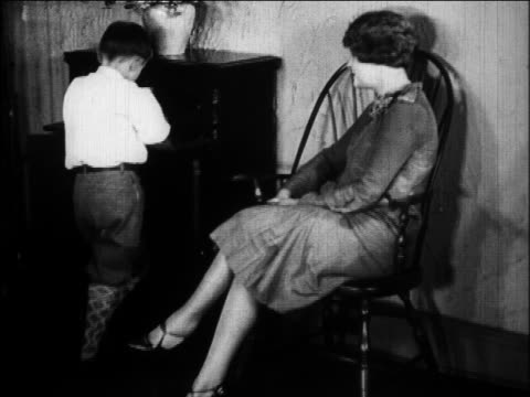 vidéos et rushes de b/w 1924 boy listening to radio as mother sits by in living room / newsreel - 1924