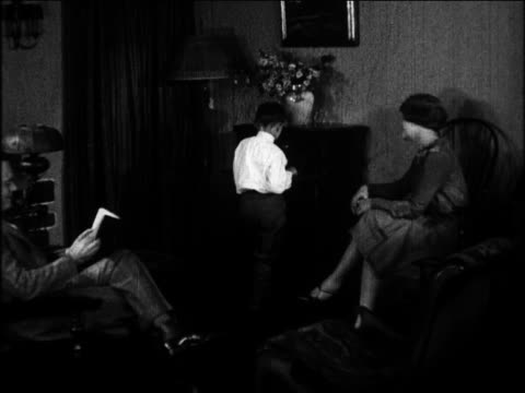 b/w 1924 boy listening to radio as parents sit in living room / newsreel - radio stock videos and b-roll footage