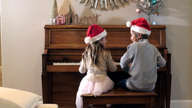 boy, little sister sitting at piano wearing santa hats - music stock videos & royalty-free footage