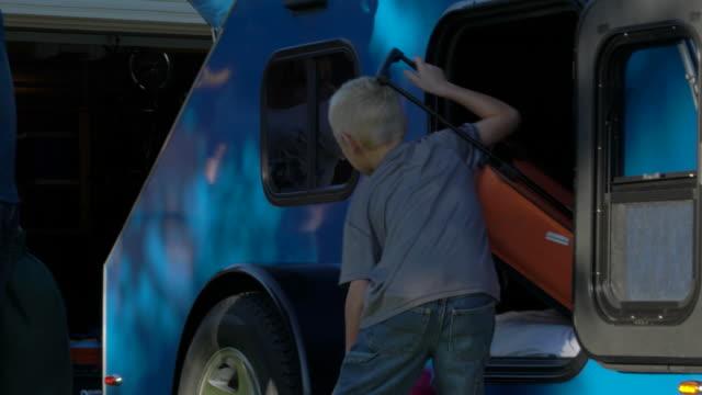stockvideo's en b-roll-footage met boy loading bags into camper, cu - aanhangwagen