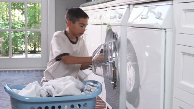 MS Boy (8-9) loading dirty laundry into washing machine, Phoenix, Arizona, USA