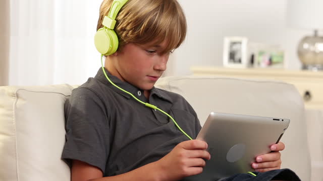 boy looking at digital tablet - one boy only stock videos & royalty-free footage