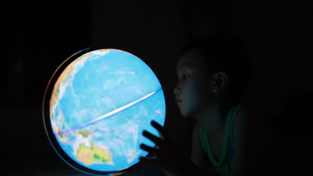 vídeos de stock e filmes b-roll de boy looking at globe - globo terrestre de escritório