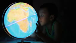 Boy looking at globe