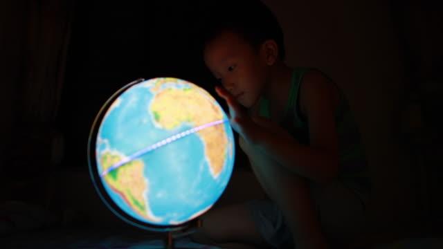 vidéos et rushes de petit garçon à la recherche du globe - découverte