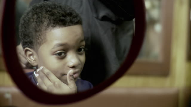 stockvideo's en b-roll-footage met cu selective focus boy (8-9) looking at his new haircut in mirror at barbershop, brooklyn, new york city, new york state, usa - spiegel